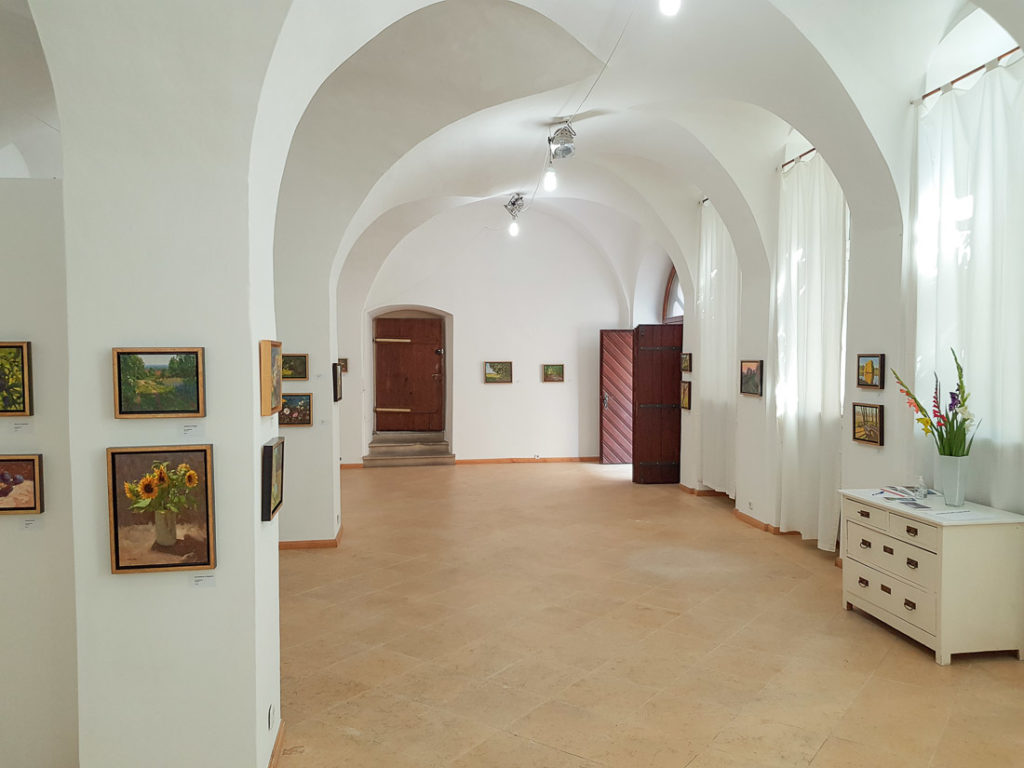 A large bright room with paintings on the wall.