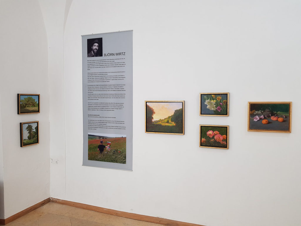 A corner of a room with white walls and paintings hanging next to a banner with information about the artist.